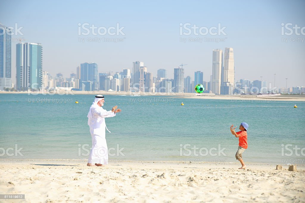 Grandfather and little boy playing ball on the beach stock photo