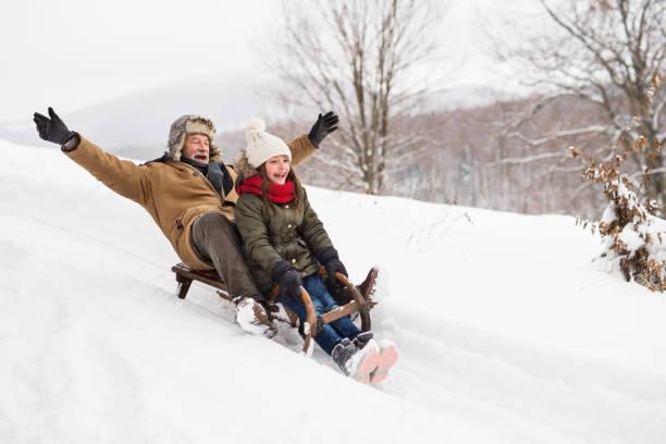 grootvader en kleine meisje sleetje rijden op een winterdag. - family winter holiday stockfoto's en -beelden