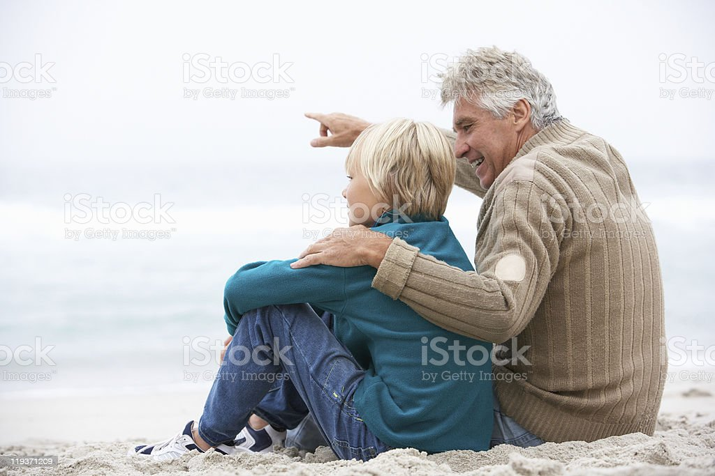 Grandfather And Son Sitting On Winter Beach Together stock photo