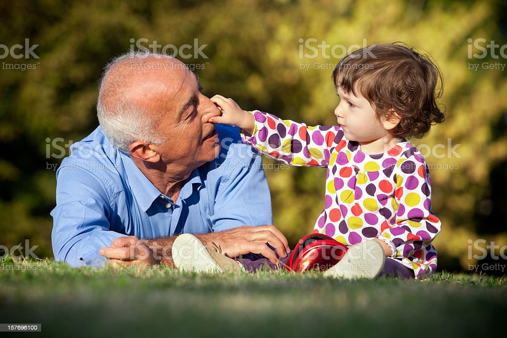 A grandfather and young granddaughter bonding at the park stock photo
