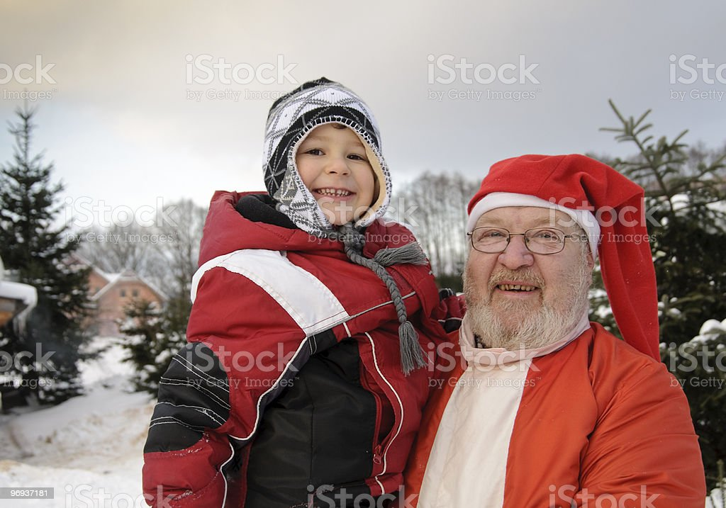 Grandfather as Santa Claus merrily with grandchild royalty-free stock photo