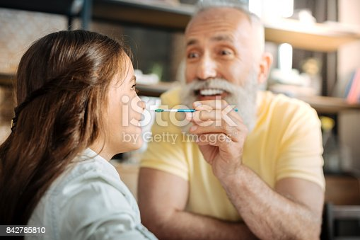 istock Grandfather being about to put paint dot on granddaughters nose 842785810