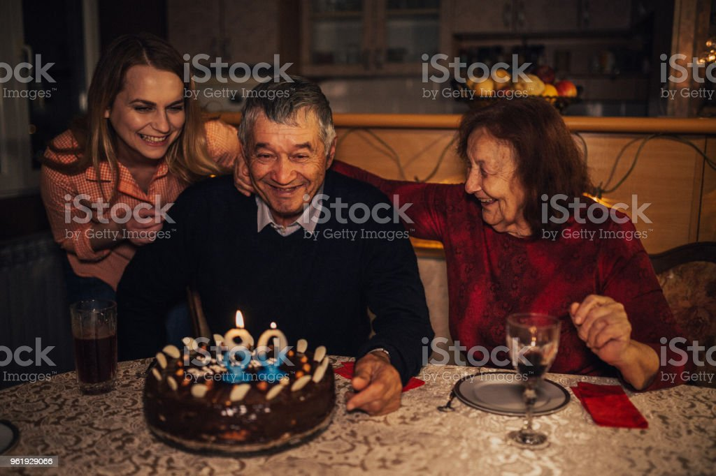 Grandfather blowing candles during his birthday celebration at home stock photo