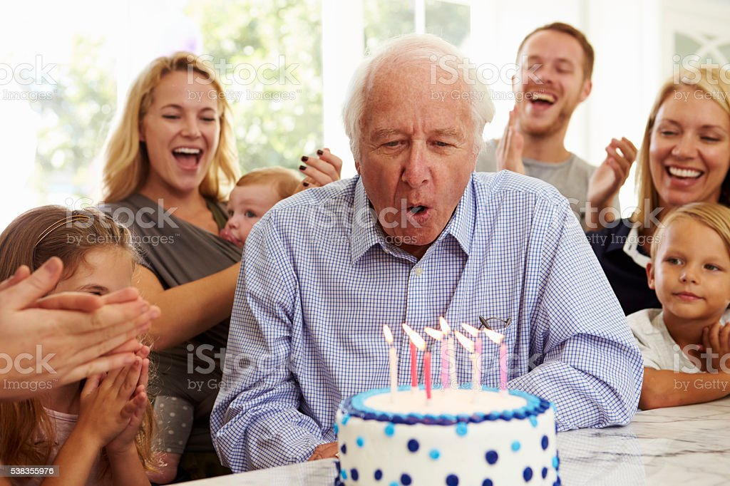 Grandfather Blows Out Birthday Cake Candles At Family Party stock photo