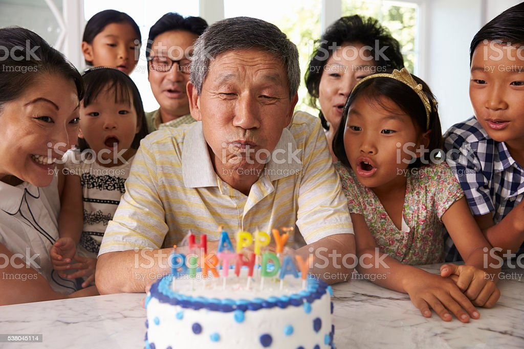 Grandfather Blows Out Candles On Birthday Cake stock photo