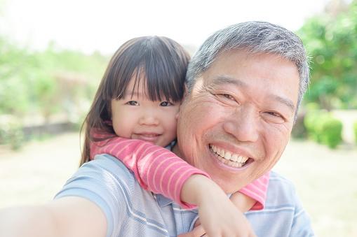 grandfather carrying cute granddaughter selfi