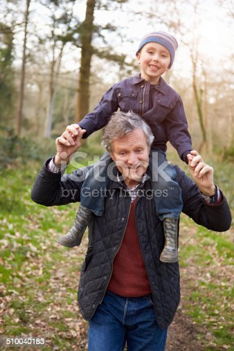 510042945 istock photo Grandfather Carrying Grandson On Shoulders During Walk 510040183