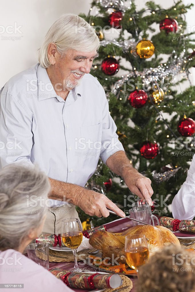 Grandfather carving turkey at christmas royalty-free stock photo