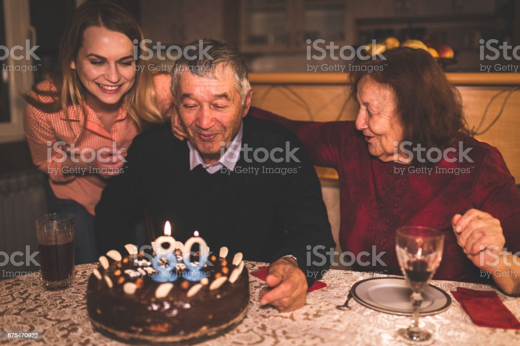 Grandfather celebrating birthday with his family at home stock photo