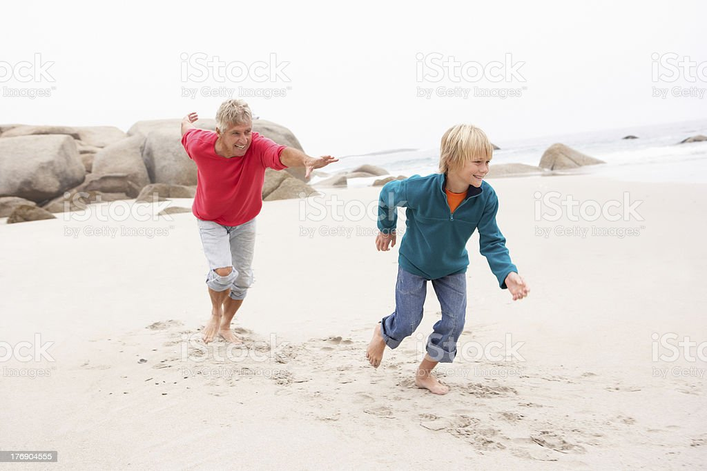 Grandfather Chasing Grandson Along Winter Beach stock photo