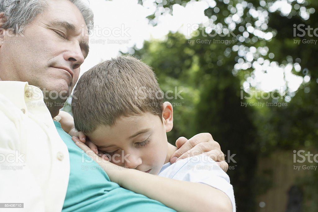Grandfather comforting grandson outdoors royalty-free stock photo