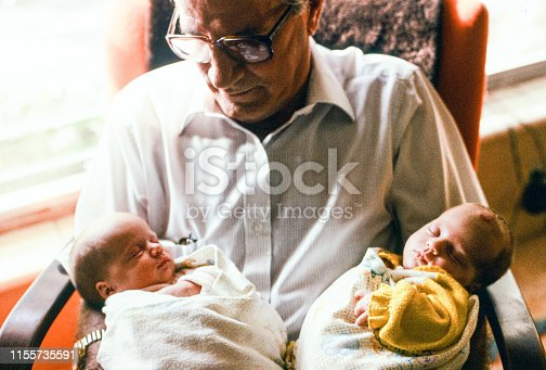 A horizontal image of a grandfather sitting near a window looking at his newborn grandchildren cradled in his arms. He is a retired man wearing a white shirt and glasses, and looking down at one of the girls. The image evokes a warm and tender moment.