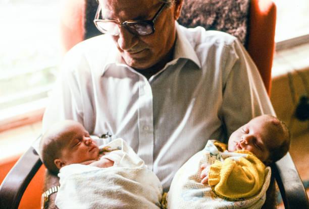 dziadek w ramionach wygrzewania się ze swoich nowo narodzonych bliźniaczych dziadków. - archiwalny zdjęcia i obrazy z banku zdjęć