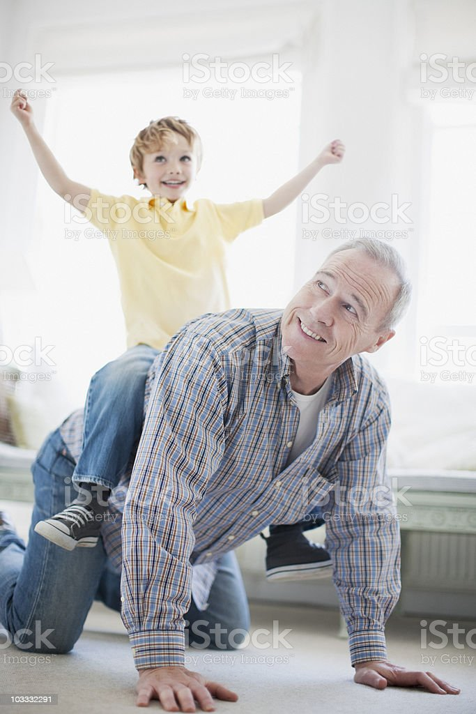 Grandfather crawling with grandson on back royalty-free stock photo