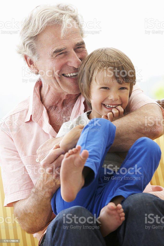 Grandfather Cuddling Grandson On Garden Seat royalty-free stock photo