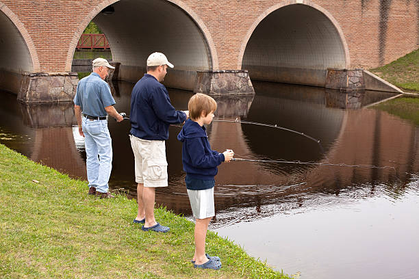 Grandfather, dad, and son fishing together. Multi-generations. Pond, park. stock photo