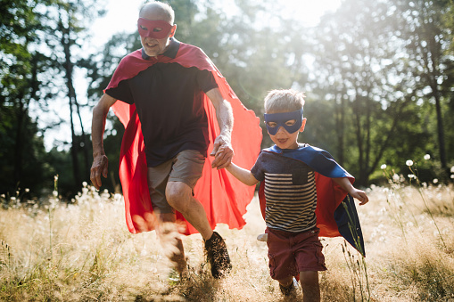 Grandfather Dressed As Superhero Plays Outside With Grandson