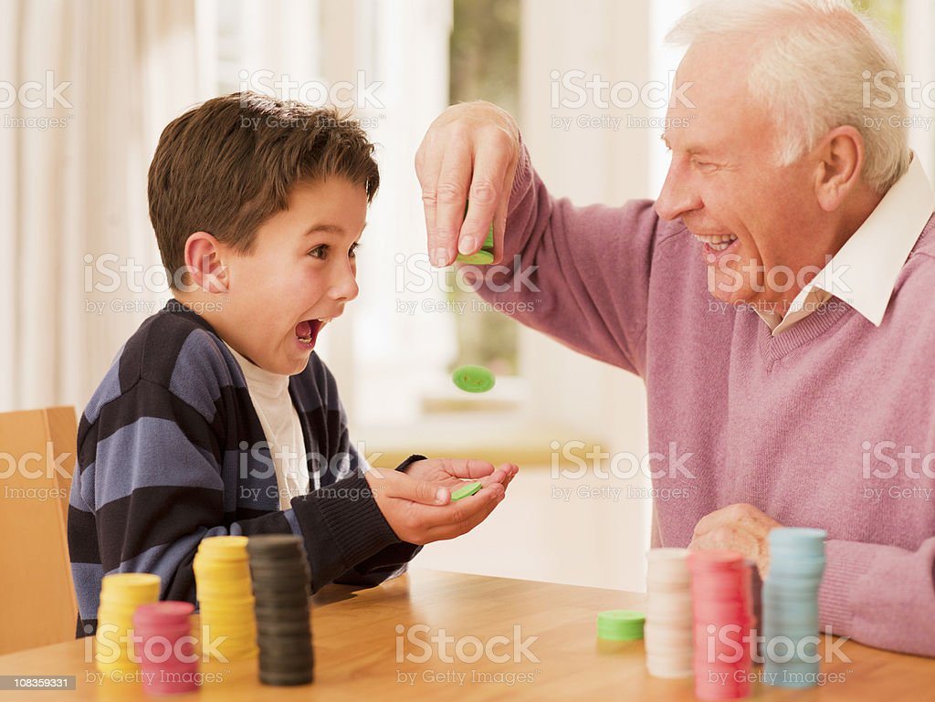 Grandfather dropping poker chips into grandsons hands royalty-free stock photo