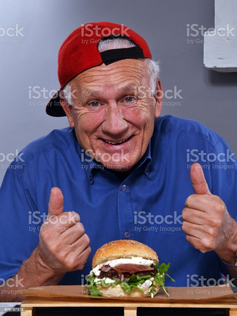 Grandfather eat hamburger royalty-free stock photo