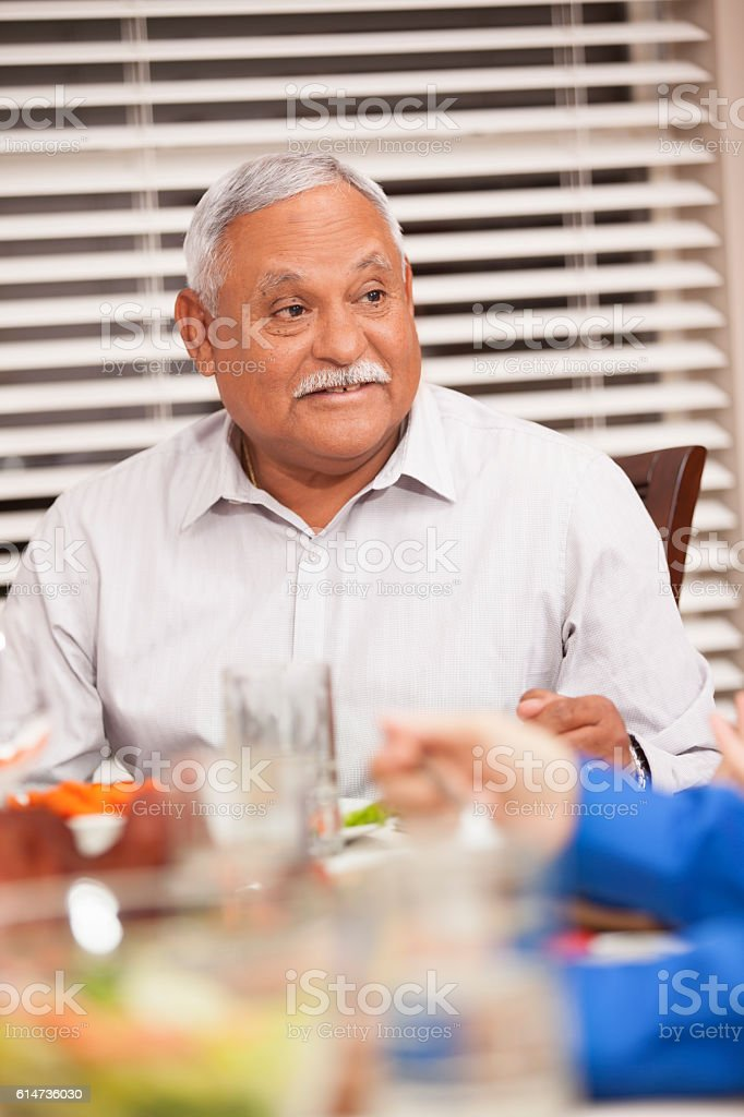 Grandfather eating holiday dinner with family. - foto de stock