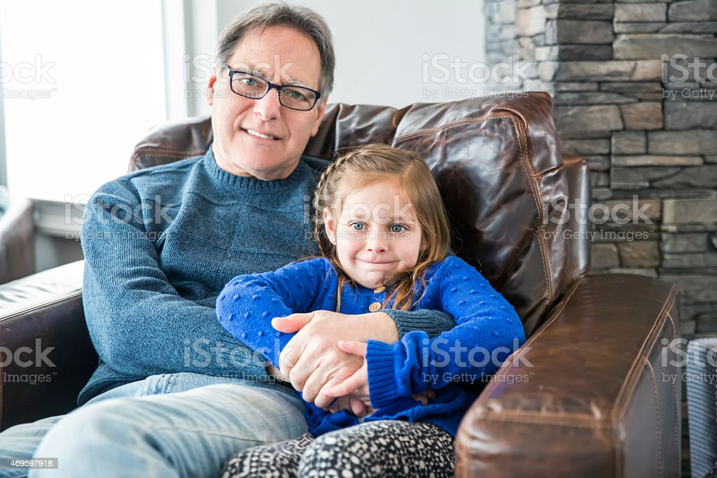 Grandfather enjoys sitting with his adorable grandaughter stock photo