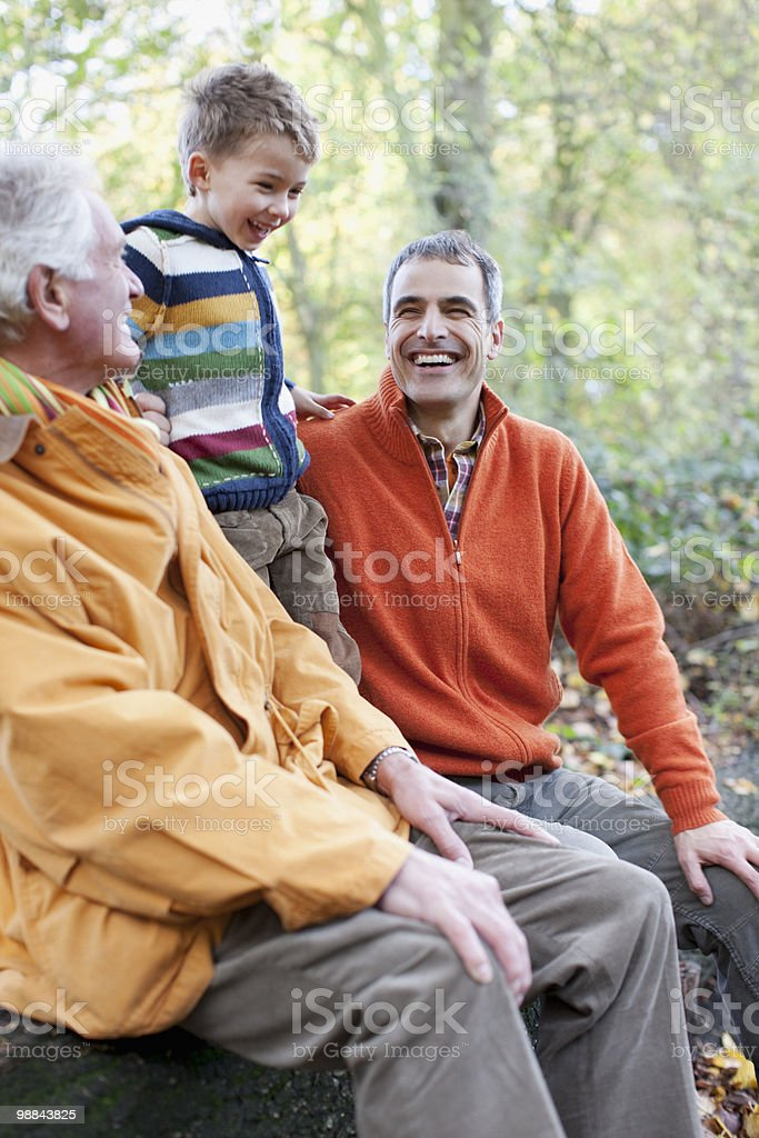 Grandfather, father and son laughing outdoors royalty-free stock photo