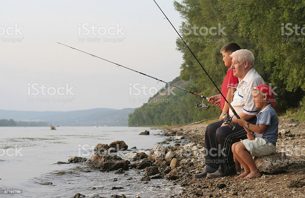 A grandfather fishing with his boys in the afternoon stock photo