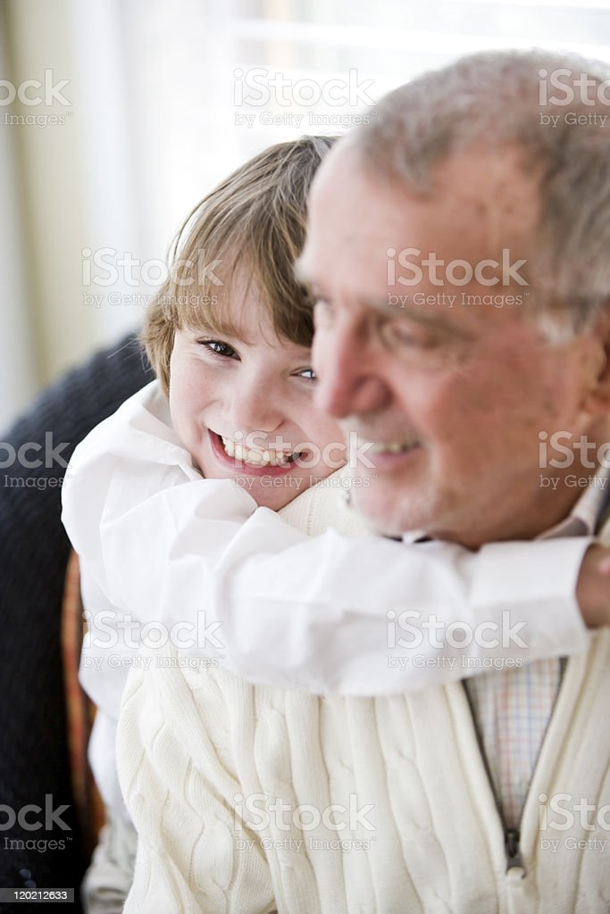 Grandfather getting hug from grandson royalty-free stock photo