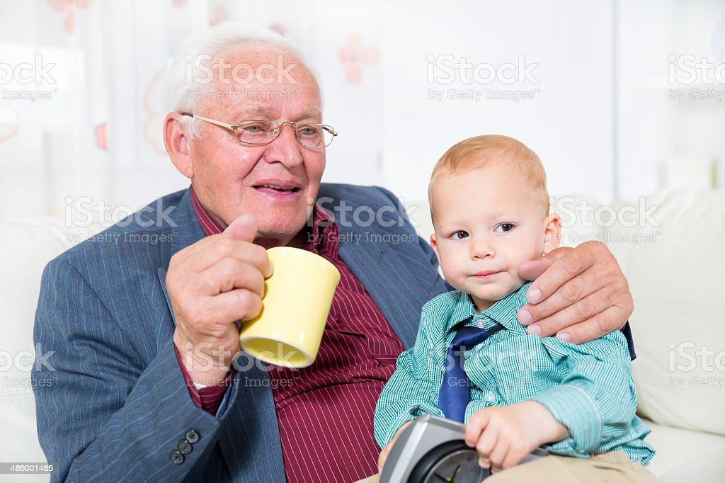 Grandfather gives his grandson a cup of milk royalty-free stock photo