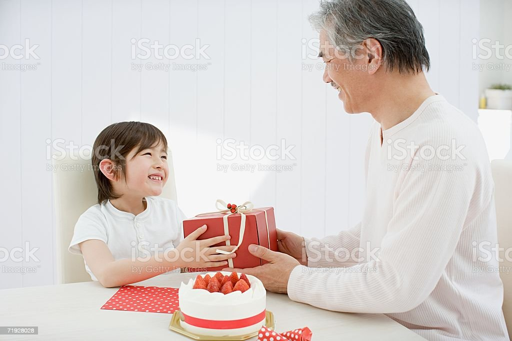 Grandfather giving boy a present royalty-free stock photo