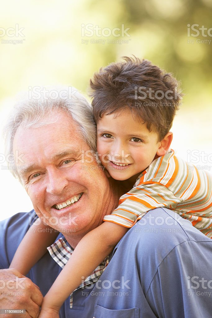 Grandfather Giving Grandson Ride On Back stock photo
