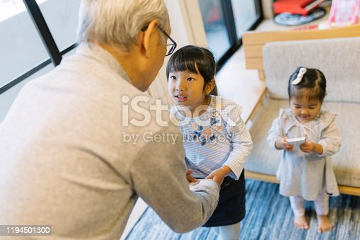 Grandfather giving New Years money to granddaughters.