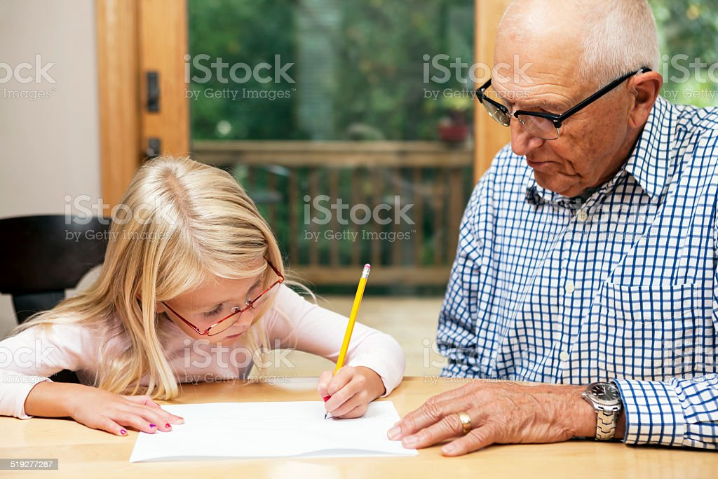 Grandfather Helping Granddaughter with Homework stock photo