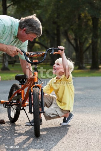 853720192 istock photo Grandfather helping little boy with bicycle 170105613