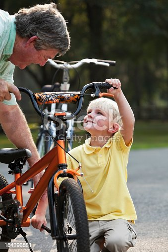 853720192 istock photo Grandfather helping little boy with bicycle 184296881