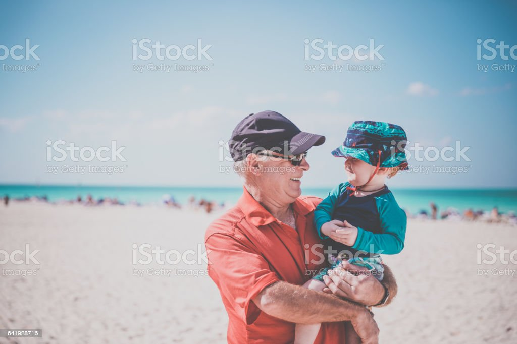 Grandfather Holding Baby Boy on Tropical Beach, Cuba stock photo