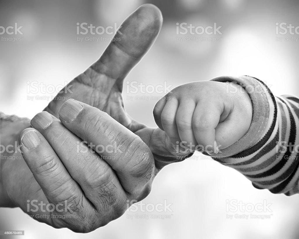 A grandfather holding his grandchild's hand stock photo