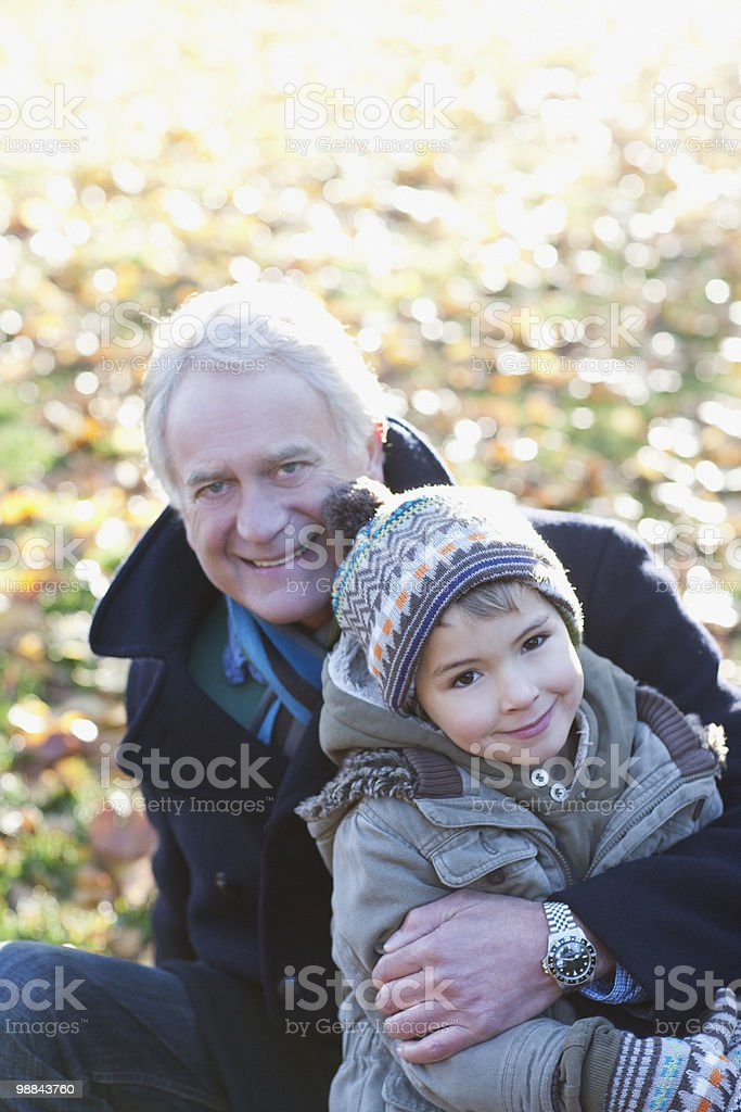 Grandfather hugging grandson outdoors in autumn royalty-free stock photo
