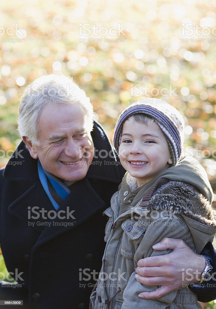 Grandfather hugging grandson outdoors 免版稅 stock photo
