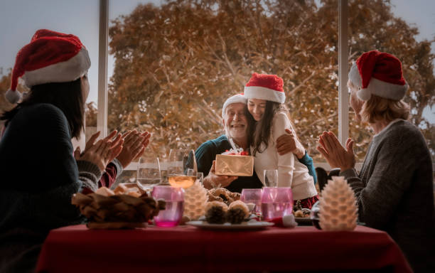 Grandfather is kissing his granddaughter after giving presents on Christmas day. stock photo