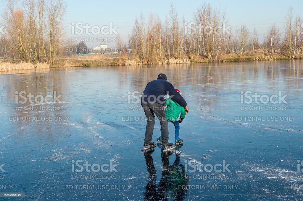 Grandfather is teaching grandson skating stock photo