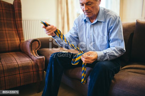 Grandfather is tying tie for granddaughter