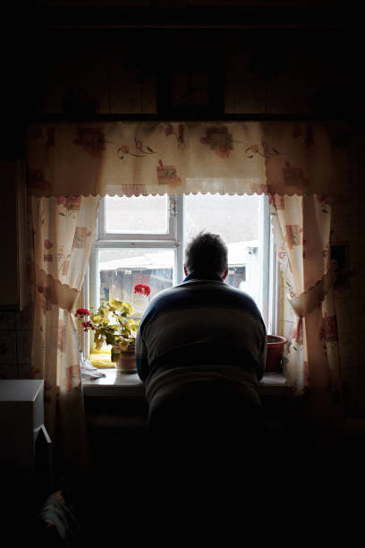 avô olha pela janela - old men window imagens e fotografias de stock