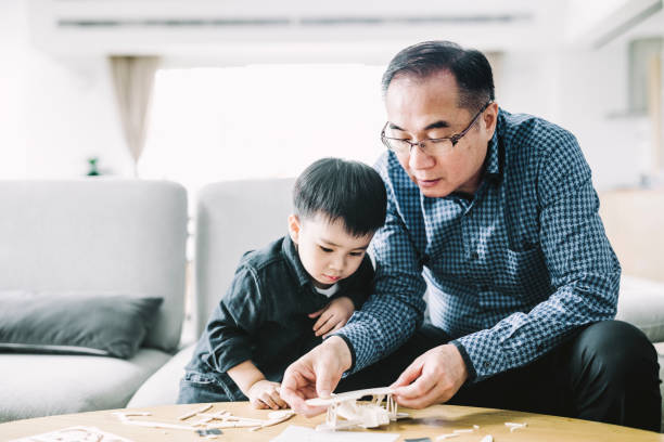 Grandfather making airplane toy for cute grandson stock photo