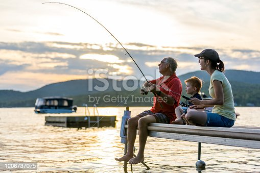 A grandfather, mother and  grandson are fishing during sunset in summer. They are all sitting on the dock and are concentrated on their activity. It is a beautiful summer day. Across the lake, there is a mountain.