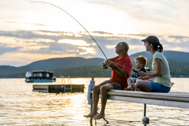 Grandfather, Mother and Grandson Fishing At Sunset in Summer stock photo