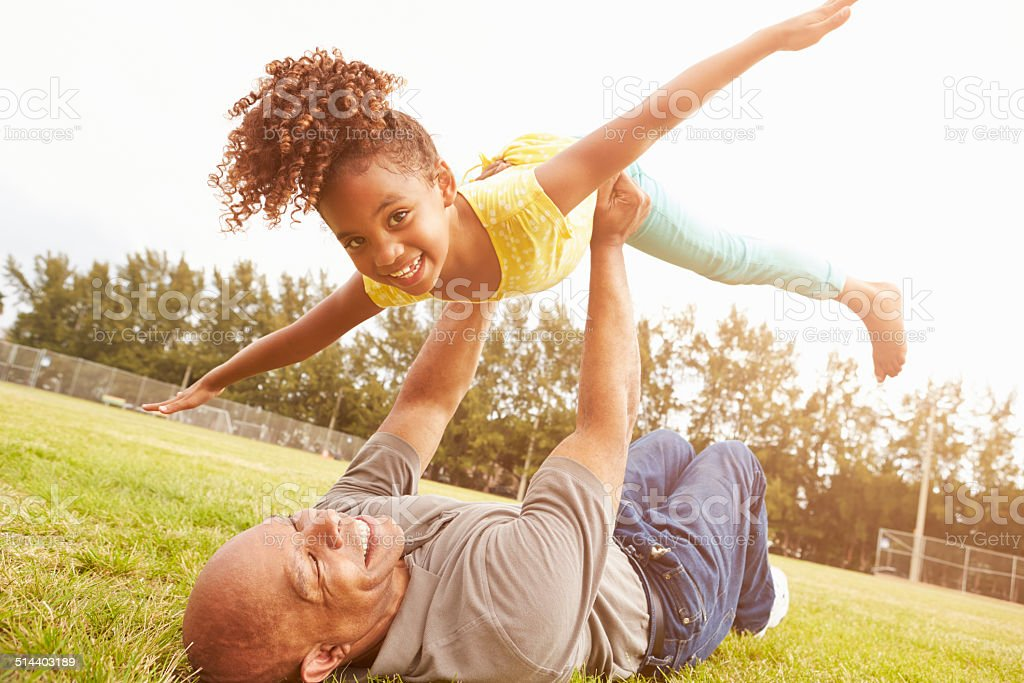 Grandfather Playing Game With Granddaughter In Park stock photo