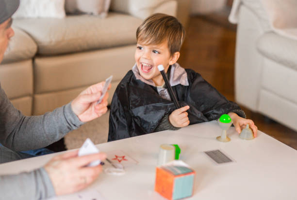 Grandfather playing magic with his grandson Grandpa Magician entertains his grandson, fun family time magic trick stock pictures, royalty-free photos & images