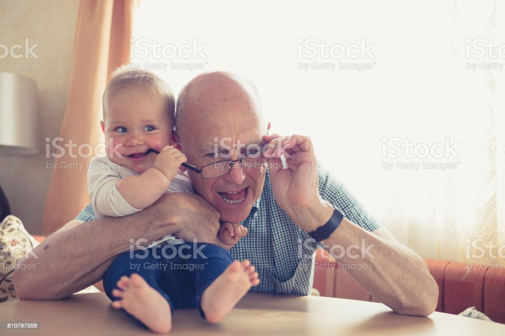 Grandfather playing with baby at table stock photo