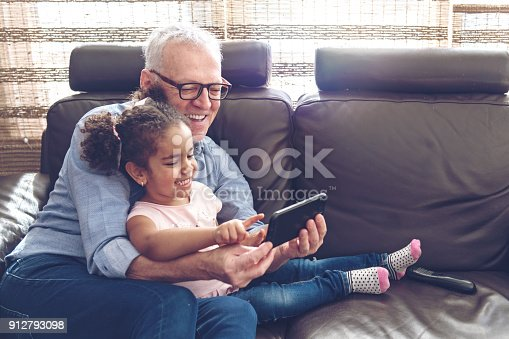 istock Grandfather playing with granddaughter on a mobile 912793098
